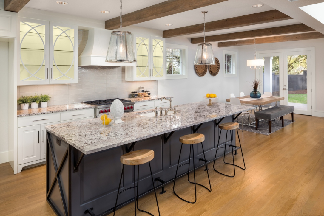 beautiful kitchen with lights on in new luxury home with island, pendant lights, and glass fronted cabinets, and view of dining room