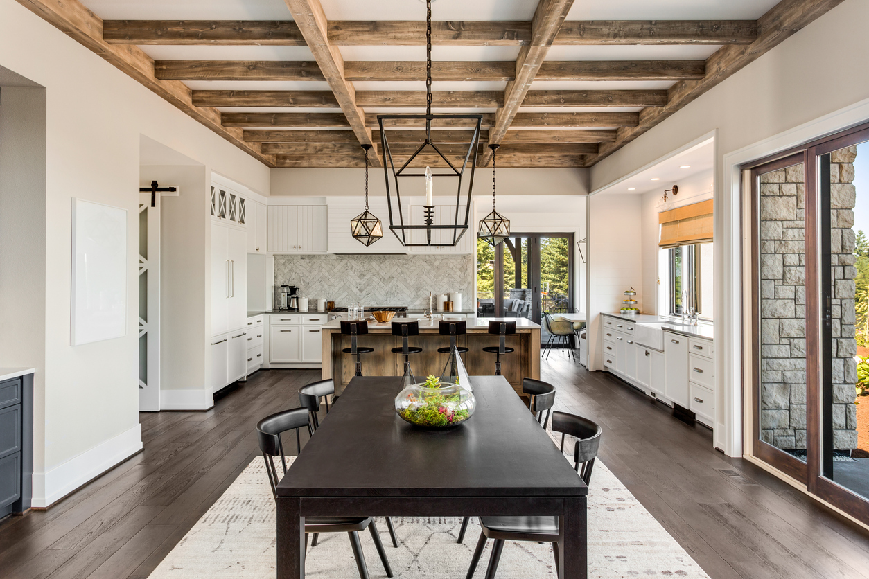 Stunning kitchen and dining room in new luxury home. Wood beams and elegant pendant lights accent this beautiful open-plan dining room and kitchen
